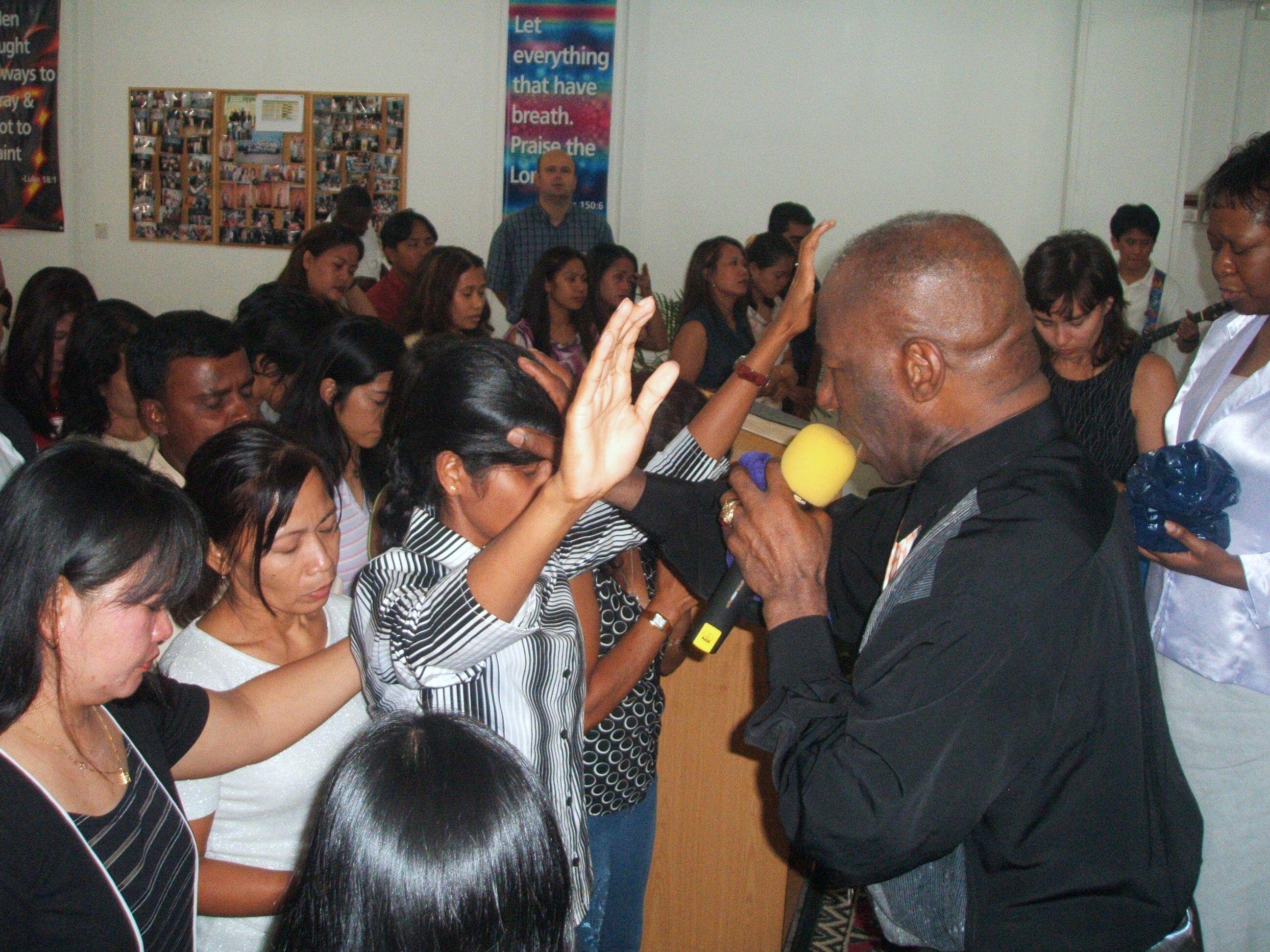 Apostle McFarlane praying for sick in the Philippines