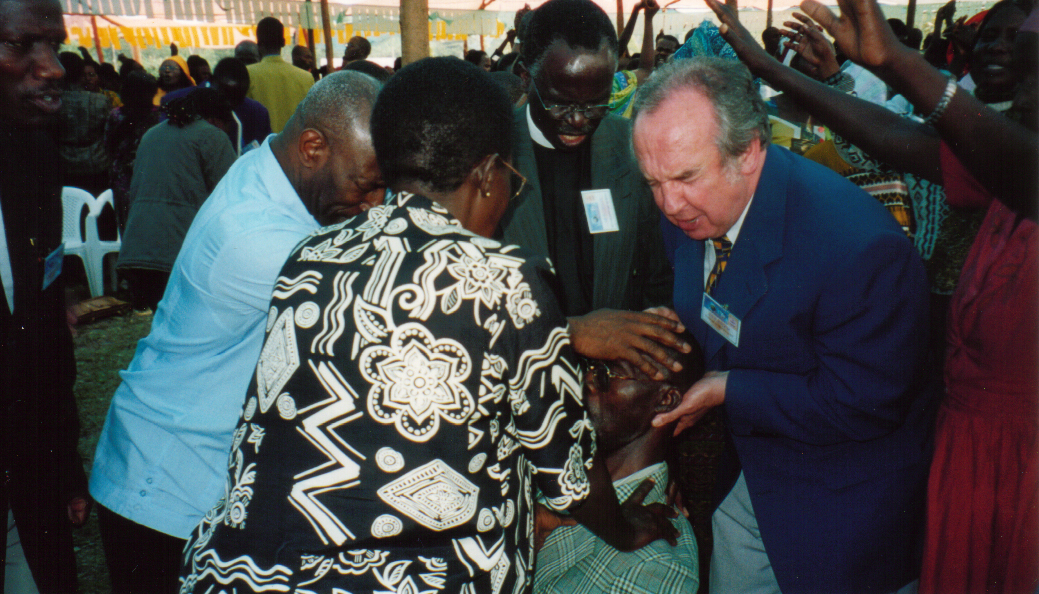 Apostle McFarlane praying for the sick in Uganda Revival