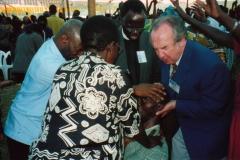 Apostle McFarlane praying for the sick in Uganda Revival
